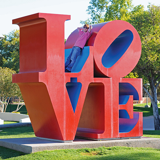 Carter sitting on Robert Indiana's LOVE Sculpture in Scottsdale Arizona, photo by Tom Grotta