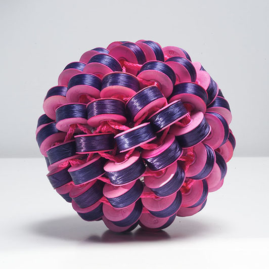 "PURPLE MEETS PINK Axel Russmeyer, polyester thread on cardboard bubbins, nylon thread, ribbon, aluminum, 5"" (d), 2010."