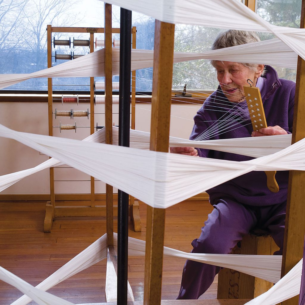 "Ethel Stein preparing a warp for her 2008 browngrotta exhibition and Monograph ""Ethel Stein: Weaver"". Photo by Tom Grotta"