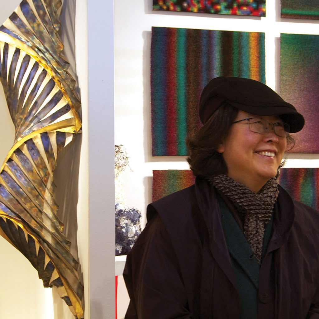 Jin-Sook So  in front of one of her Untitled Steel Mesh wall sculptures at SOFA NY 2011. Photo by Carter Grotta